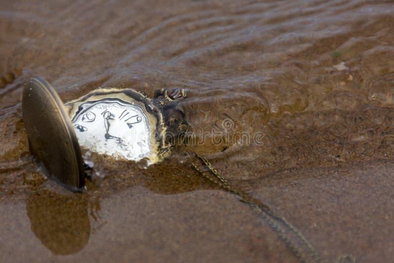Relojes de bolsillo redondos en la arena debajo del agua imagen de archivo libre de regalías