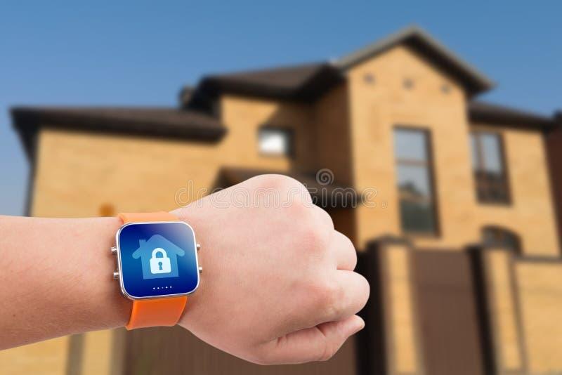 Relojes de Smart con la seguridad en el hogar app en una mano en el fondo del edificio fotos de archivo