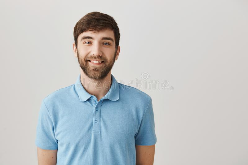 Rely only on true friends. Indoor shot of positive good-looking man with beard smiling friendly and happily while royalty free stock images