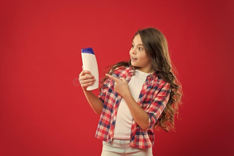Remédios capilares Garota de cabelo crespo segurando garrafa de champô Criança pequena no fundo vermelho conceito de Hairdresser  fotografia de stock