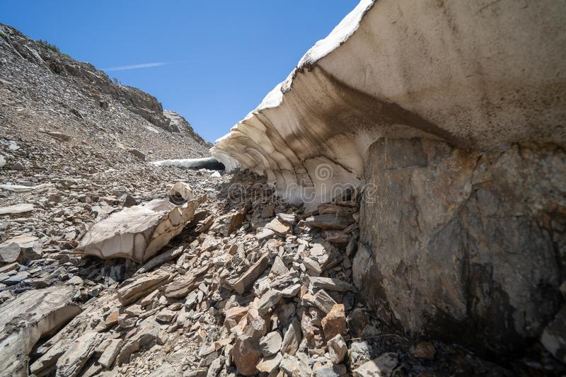 Remaining snow cave along the trail of the 20 Lakes Basin hike in California. In summer stock photography