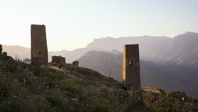 The remains of the aul of the ghost Goor in Dagestan in the evening. Ruins and towers of the aul ghost Goor in Dagestan in the evening light royalty free stock image