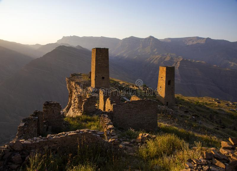 The remains of the aul of the ghost Goor in Dagestan in the evening. Ruins and towers of the aul ghost Goor in Dagestan in the evening light stock image