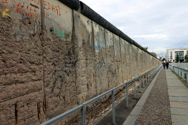 Remains of Berlin Wall Near Checkpoint Charlie. Tourists walk alongside the crumbling and graffiti painted remains of the Berlin Wall located across from the stock images