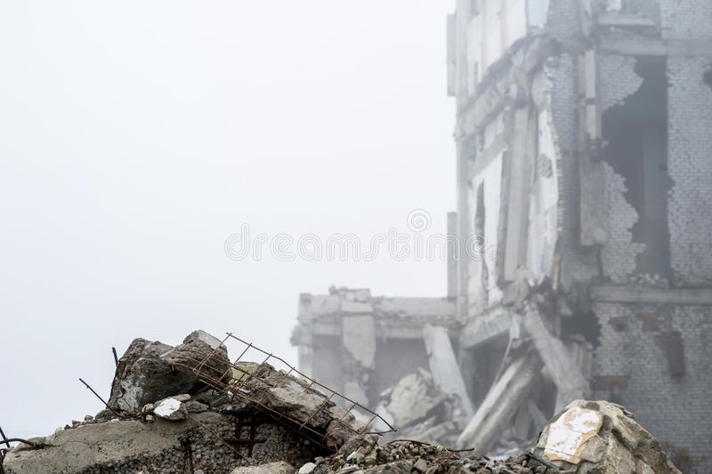 The remains of concrete fragments of gray stones on the background of the destroyed building in a foggy haze. Copy space stock images