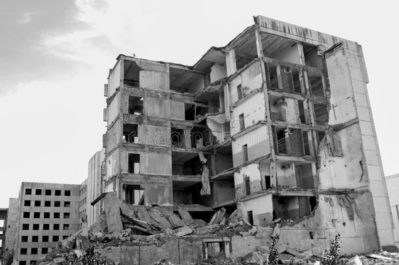 The remains of a destroyed concrete building against the sky. Black and white. Background stock image