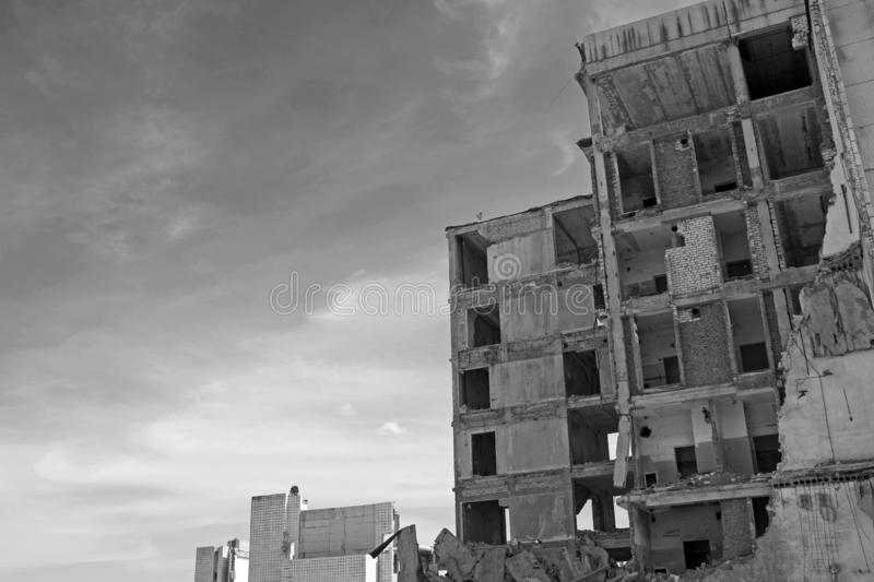 The remains of a destroyed concrete building against the sky. Space for text. Black and white. Background stock images