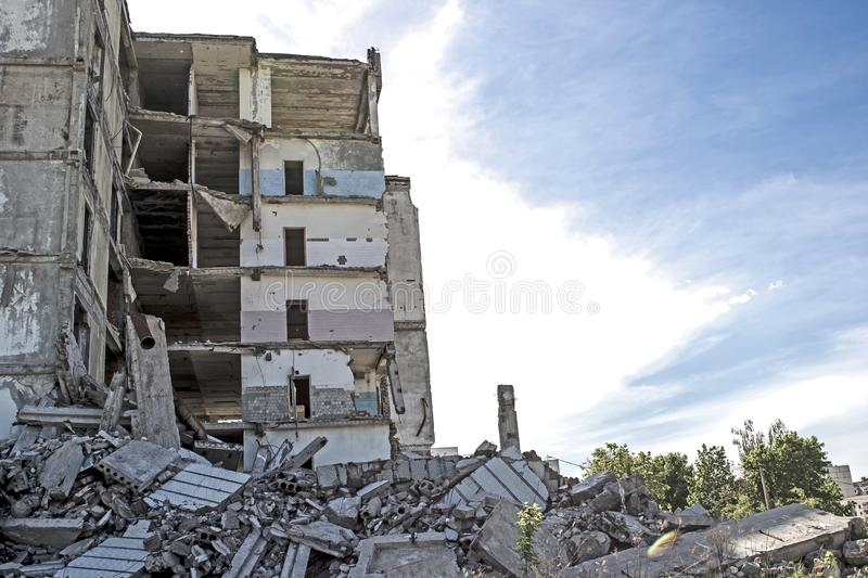 The remains of the destroyed concrete building against the textured blue sky. Space for text. Background stock photo