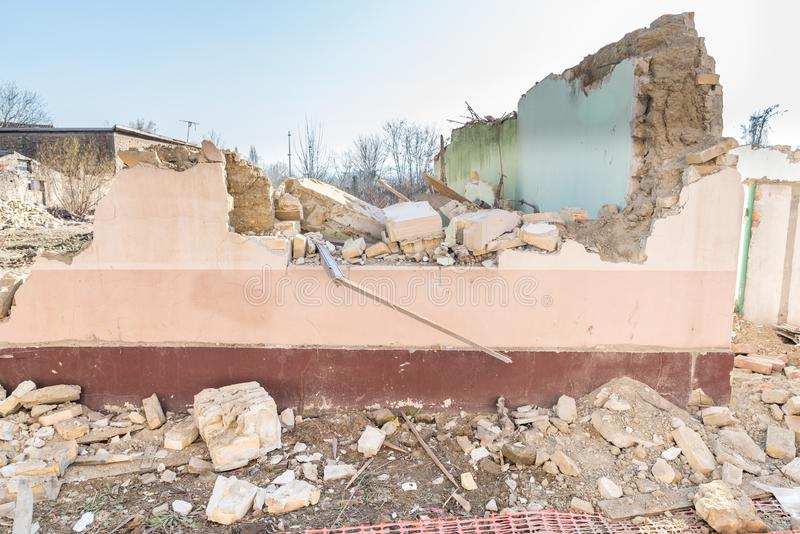 Remains of hurricane or earthquake aftermath disaster damage on ruined old houses with collapsed roof and wall royalty free stock photo