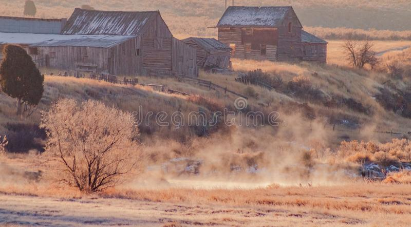Old Farm Next to a Steaming Creek. The remains of an old abandoned farm from the turn of the century sits next to a creek with steaming water from the cold royalty free stock image