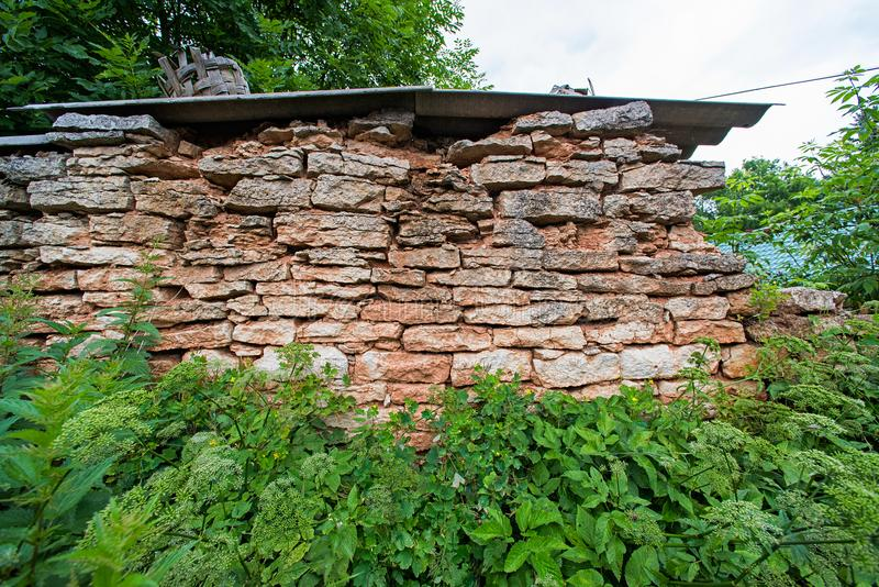 Remains of an old wall abandoned in the grass royalty free stock photo