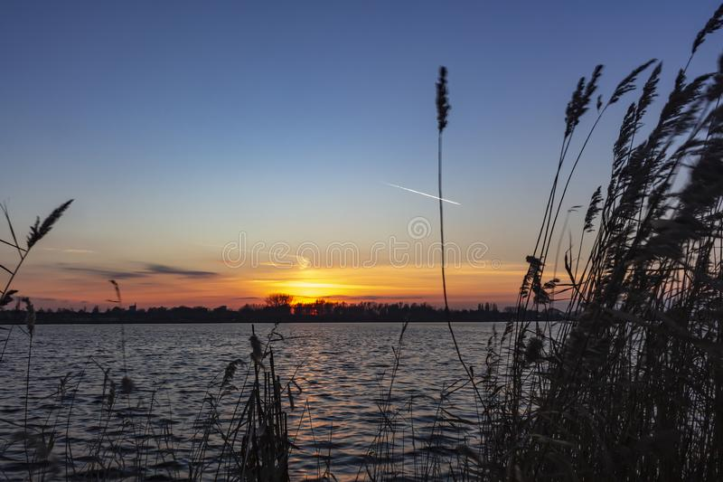 The remains of the pearly sky are visible and colors the sky above the cane of lake Zoetermeerse plas in Zoetermeer, Netherlands b. The remains of the pearly sky royalty free stock photo