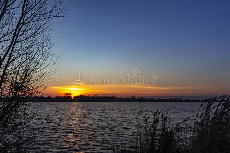 The remains of the pearly sky are visible and colors the sky above lake Zoetermeerse plas in Zoetermeer, Netherlands beautifully. The remains of the pearly sky stock photography