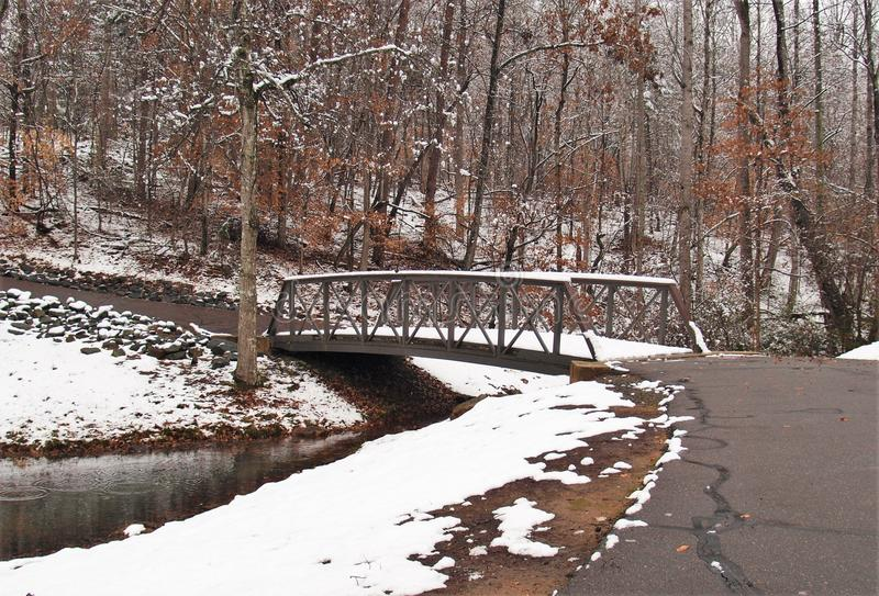 C. G. Hill Memorial Park. The remains of a snowfall cover the banks and a footbridge at C. G. Hill Memorial Park in Winston-Salem, North Carolina royalty free stock image