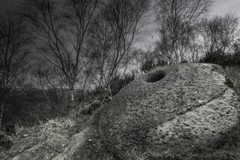 Old millstone in Derbyshire, UK. Remains of Stone Age culture.Ancient millstone used to grind barley grains and produce flour in past.Peak District, Derbyshire royalty free stock photography