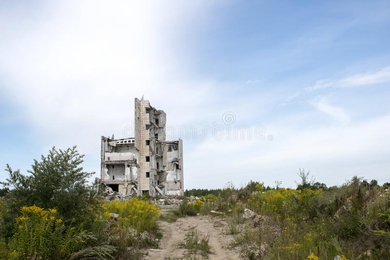 The remains of the structure of a large destroyed building with concrete gray debris around. Background. Text space stock images