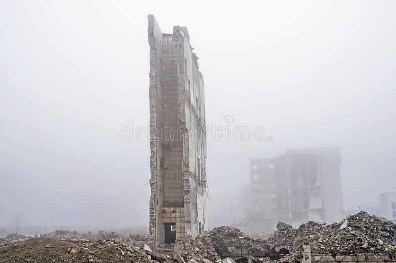 The remains of the wall of a large destroyed building against the background of other destroyed buildings stock photo