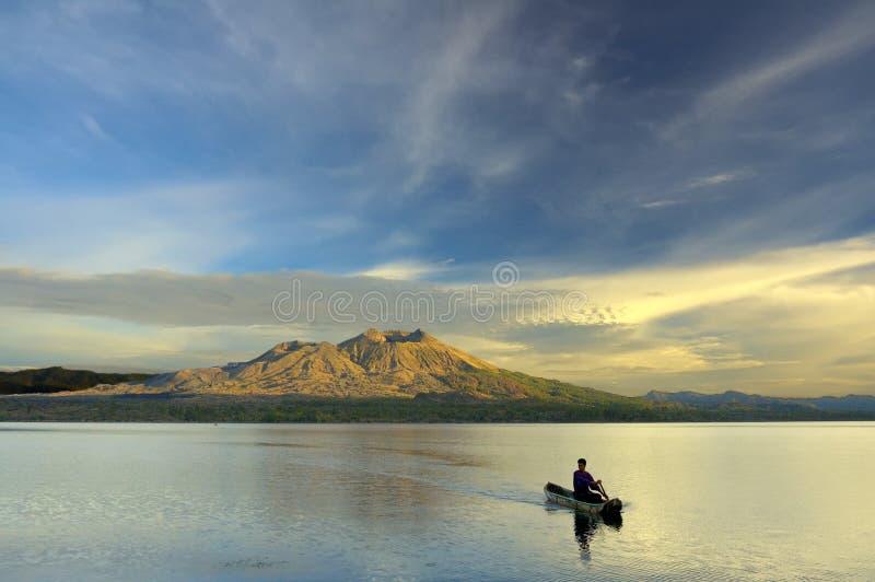Remando uma canoa no nascer do sol fotografia de stock