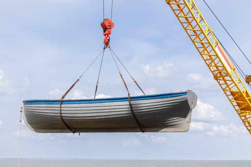 Remar el barco de madera es lanzamiento en el mar usando la grúa fotos de archivo