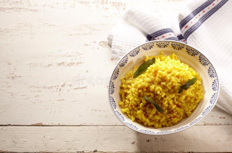 Remate abajo de la opinión sobre el cuenco de arroz amarillo con sabio foto de archivo