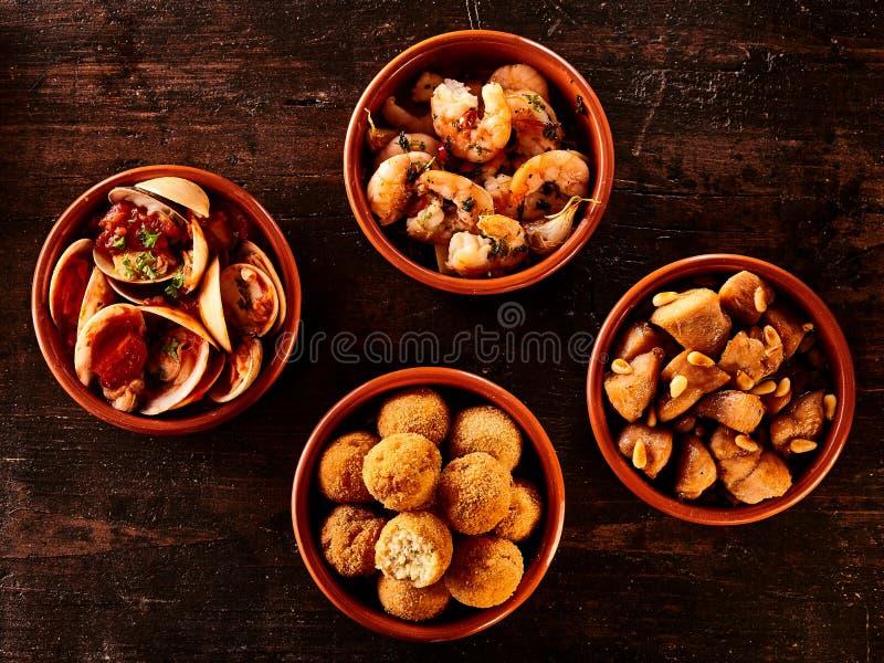 Remate abajo de la vista de aperitivos españoles en cuencos fotos de archivo