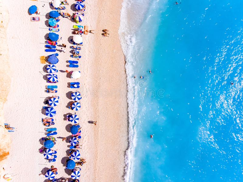 Remate abajo de vista de una playa con los suntbeds de los turistas y los wi de los paraguas foto de archivo libre de regalías