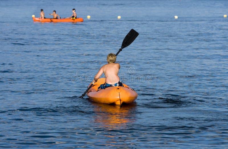 Rematura del ragazzo in una canoa immagini stock