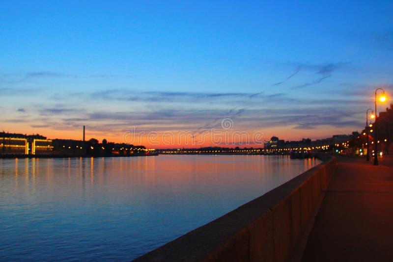 Remblai de ville au coucher du soleil. Rivi?re dans la ville la nuit photo libre de droits