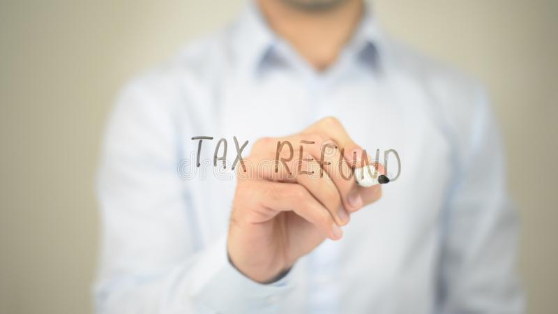 Remboursement d'impôt fiscal, écriture d'homme sur l'écran transparent images stock