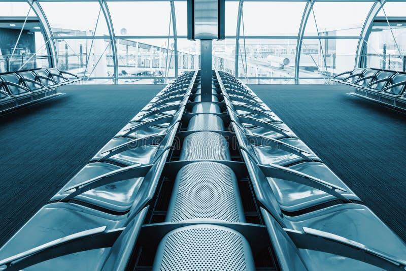 Reme los asientos para los pasajeros en el pasillo del aeropuerto En el fondo foto de archivo