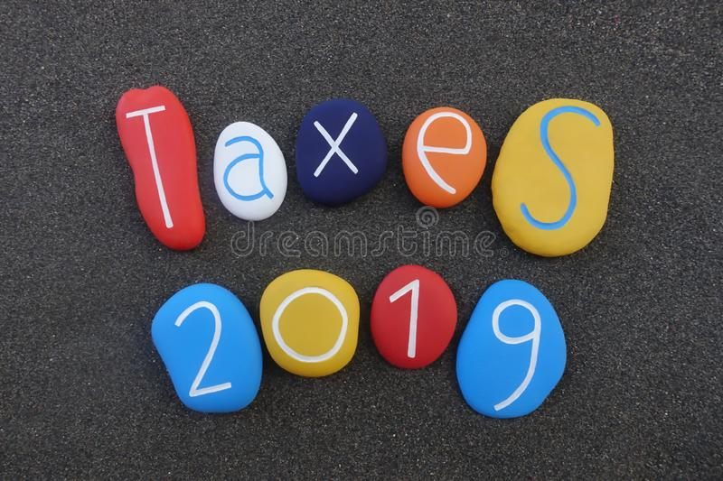Taxes 2019 text composed over black volcanic sand. Remember to pay taxes of 2019, creative text composed with multi colored stones over black volcanic sand stock photography
