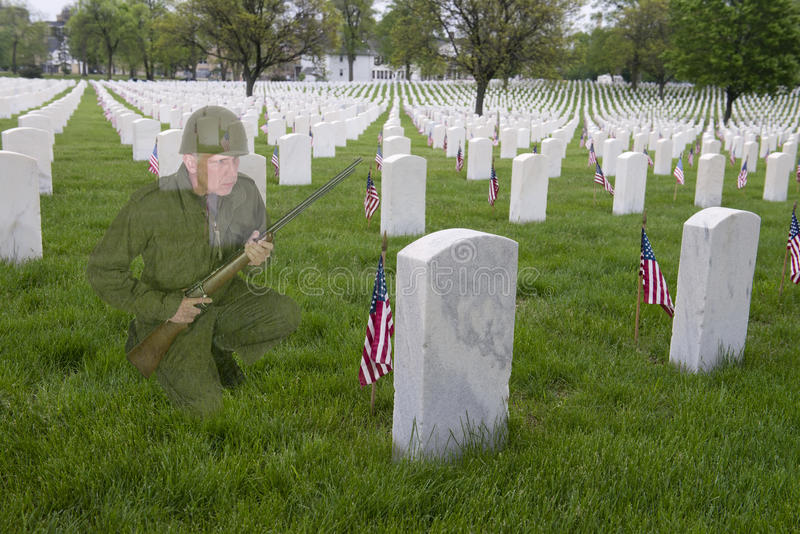 Veterans or memorial Day Concept, Soldier Cemetery. A vintage World War II military soldier kneels at the grave of a fallen comrade. The abstract concept has the stock photo