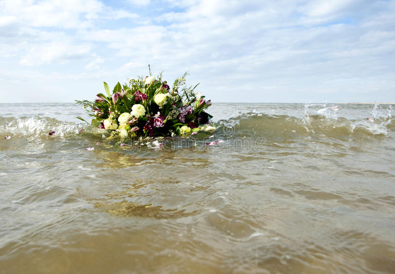 Remembrance. Bouquet afloat in the gentile surf of the north sea, as metaphor of remembrance of a watery grave royalty free stock photography