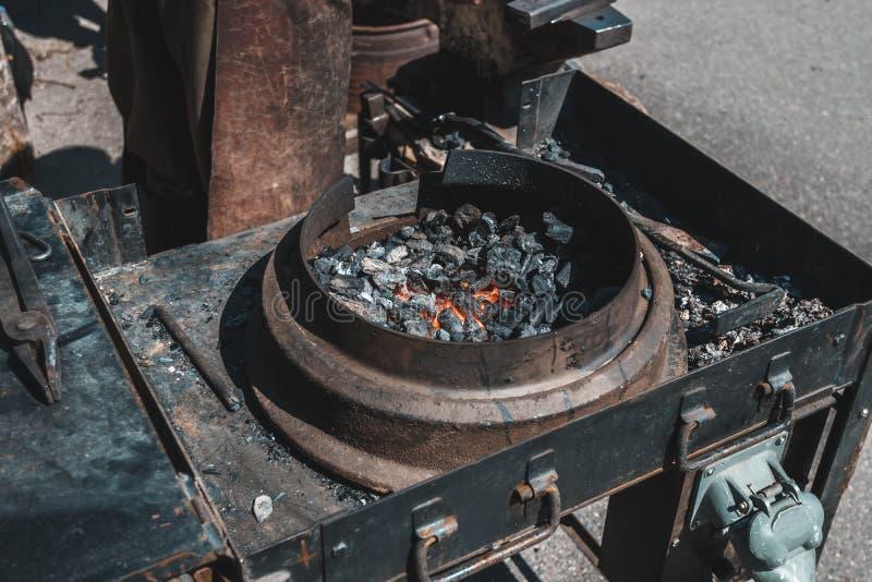 remeslic铁匠 金属nogrev的煤炭对红色 r r 免版税库存照片