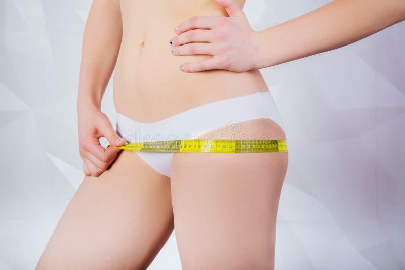 Remet la taille de mesure avec une bande Femme convenable et en bonne santé sur le fond blanc images stock