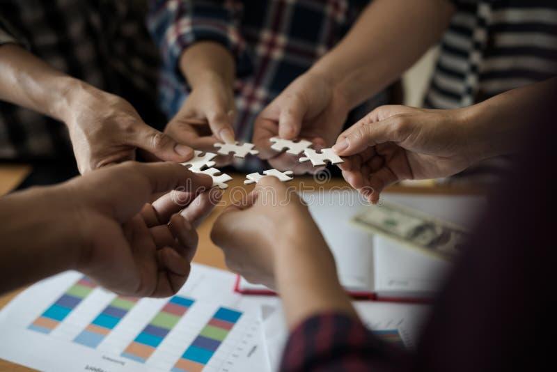 Remet le groupe de gens d'affaires assemblant le blanc de puzzle denteux B image stock