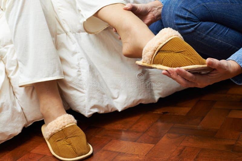 Remet les pieds de aide mettant sur des pantoufles images stock