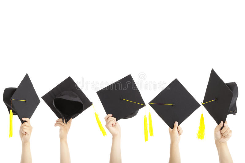 On remettent des chapeaux de graduation de fixation images stock