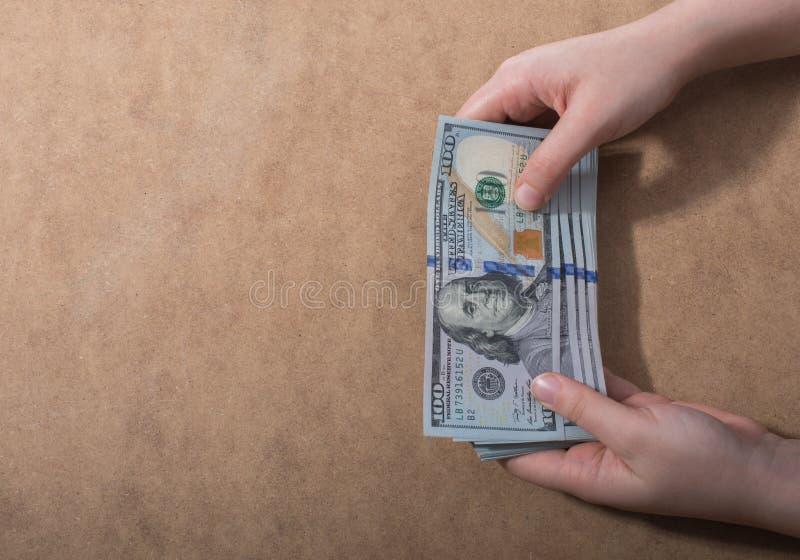 Remettez juger le dollar américain d'isolement sur le fond en bois photographie stock libre de droits