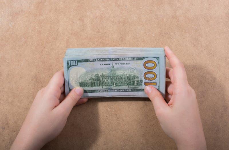 Remettez juger le dollar américain d'isolement sur le fond en bois photographie stock