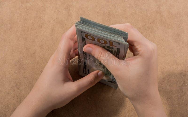 Remettez juger le dollar américain d'isolement sur le fond en bois images libres de droits