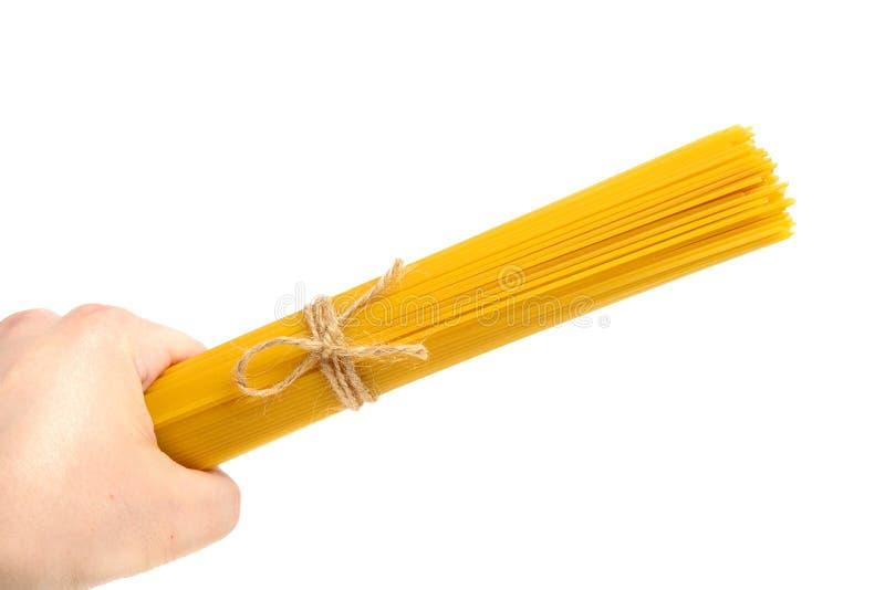 Remettez juger les pâtes ou les spaghetti jaunes d'isolement sur le blanc photo libre de droits