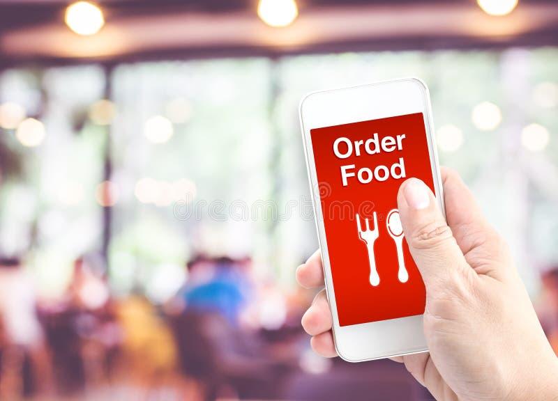Remettez juger mobile avec la nourriture d'ordre avec le backgro de restaurant de tache floue photos stock