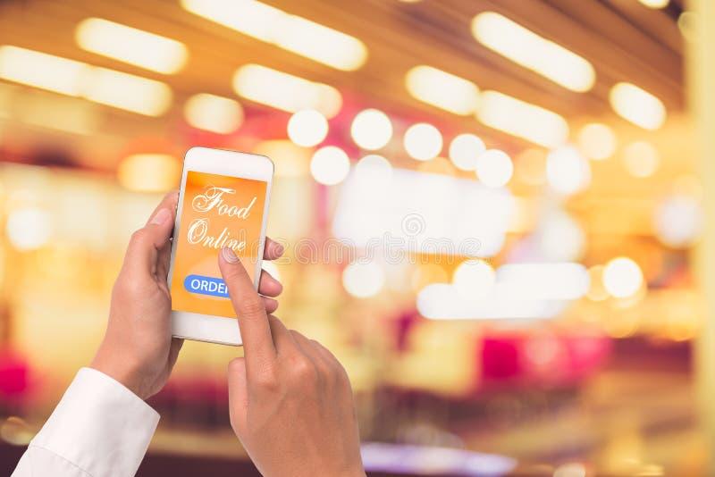 Remettez juger mobile avec la nourriture d'ordre en ligne avec le restaurant de tache floue images libres de droits