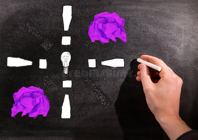 Remettez l'ampoule de dessin avec les boules de papier chiffonnées devant le tableau noir photos stock