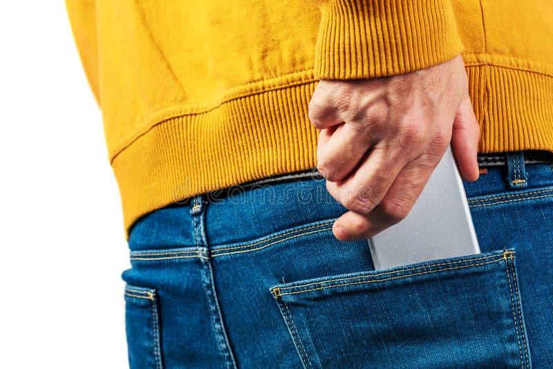 Remettez l'atteinte pour le téléphone portable dans des jeans de retour empochent photographie stock