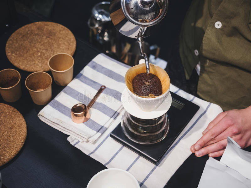 Remettez l'eau de versement de barman de café d'égouttement sur le marc de café avec le fil photographie stock libre de droits