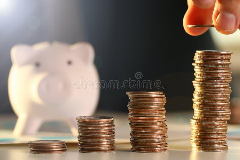 Remettez l'homme d'affaires mettant l'argent de goupille dans le porc photos libres de droits