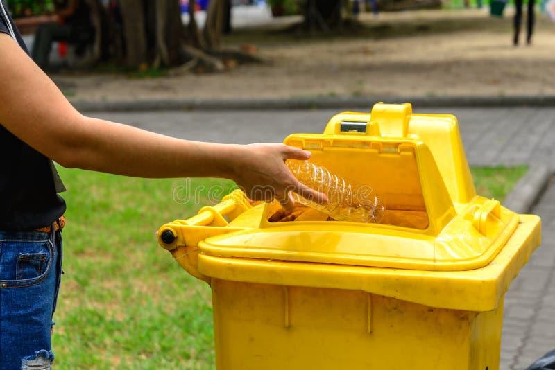 Remettez la bouteille de lancement dans le bac à ordures jaune photographie stock