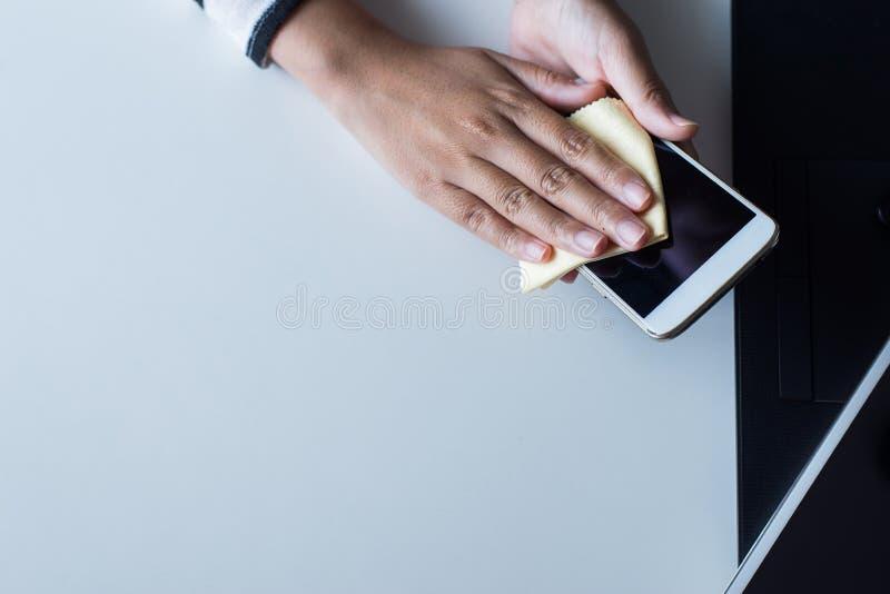 Remettez la femme nettoyant le téléphone intelligent sur l'écran avec le tissu de microfiber photo libre de droits